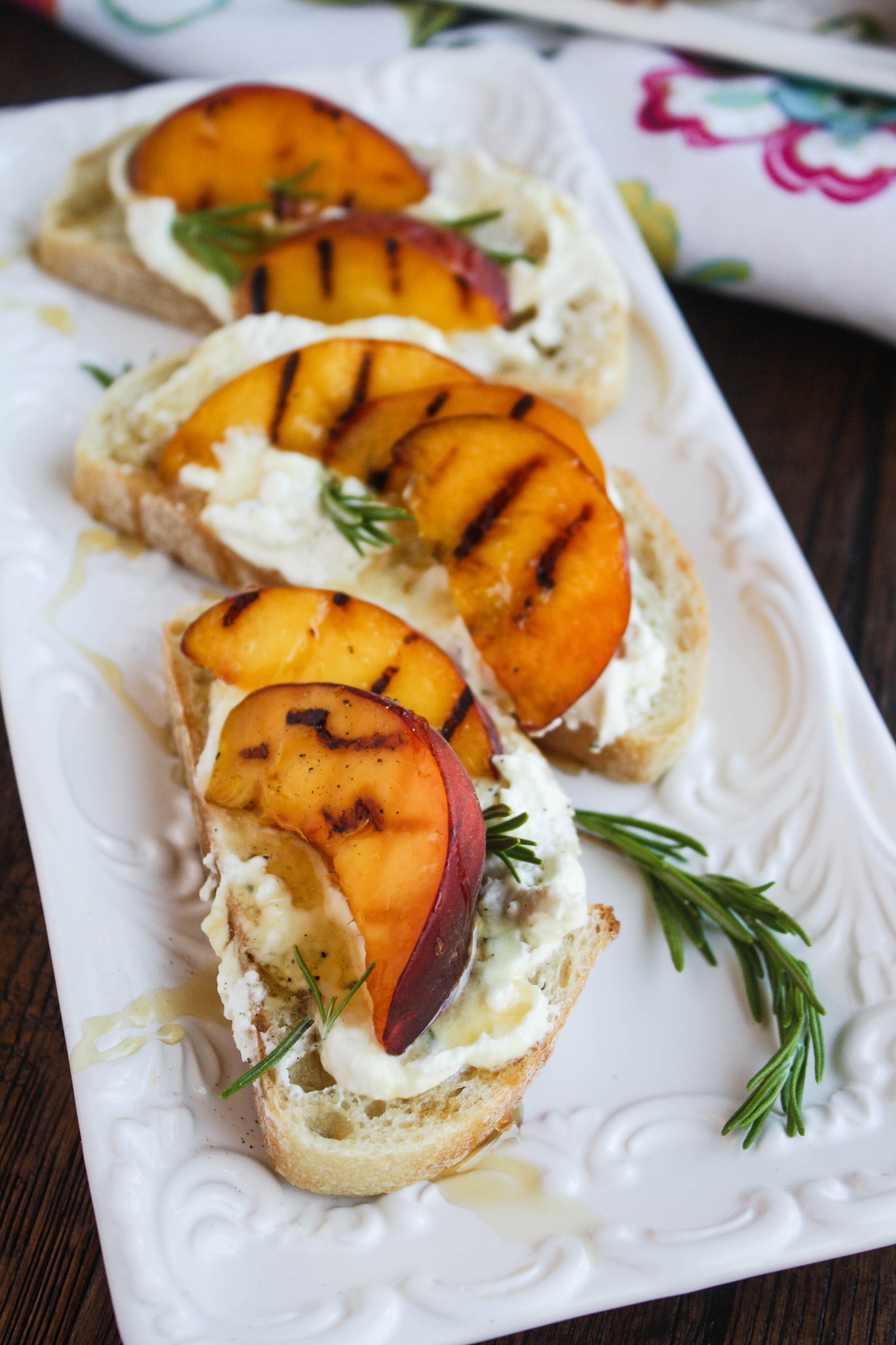 Rosemary Whipped Feta with Grilled Peaches and Honey is a lovely, cheesy appetizer. Serve it at your next party!