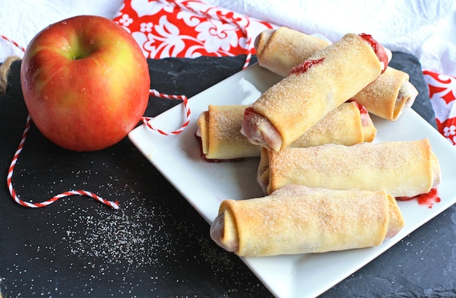 An apple next to crispy Cranberry-apple Pie Spring Rolls