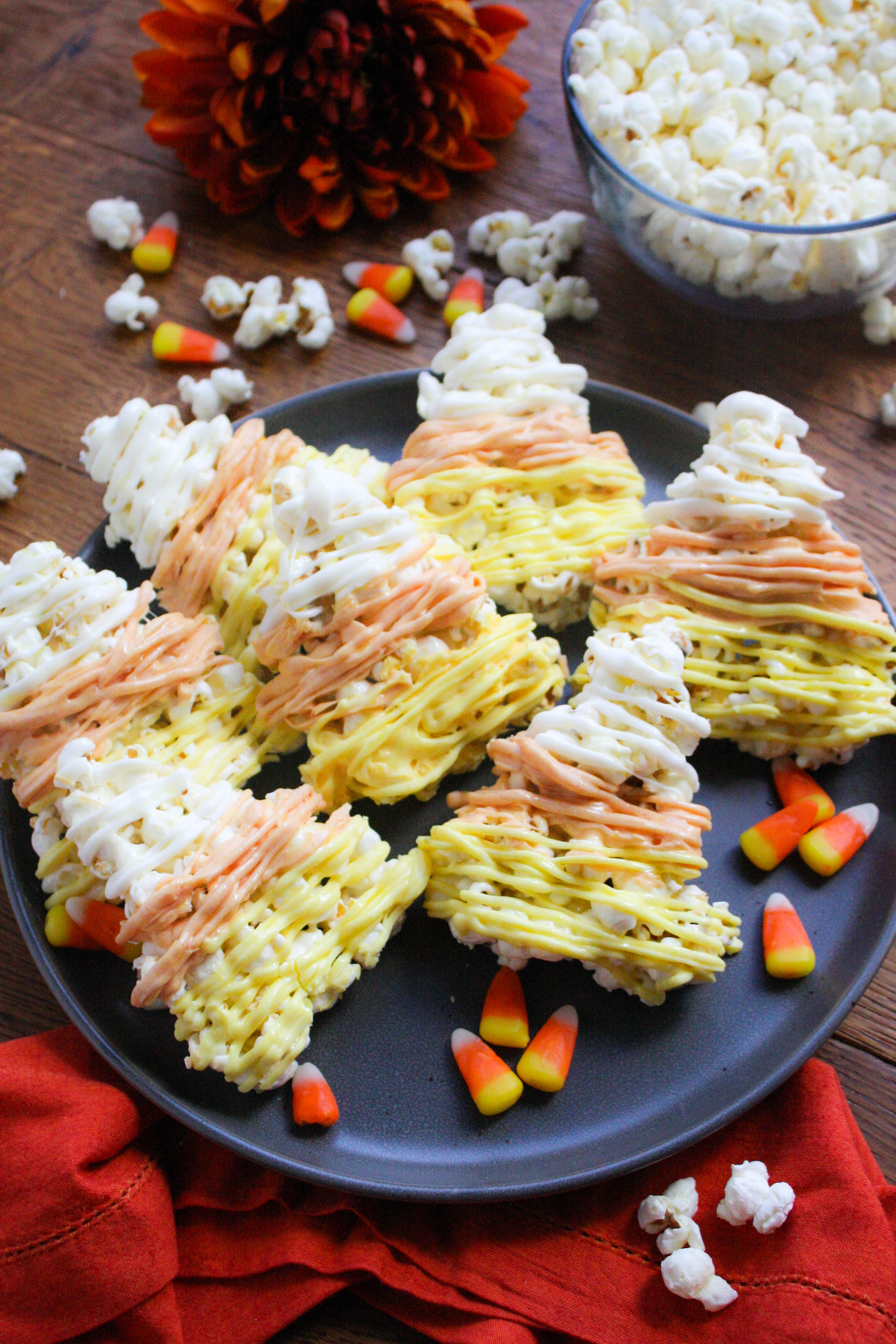 Candy Corn-Shaped Popcorn Balls are festive and fabulous for Halloween! Make these Candy Corn-Shaped Popcorn Balls for a Halloween treat!
