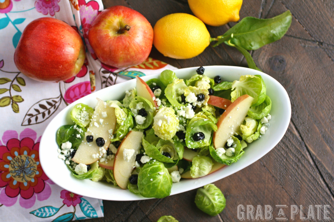 A bowl filled with a flavorful salad like Brussels Sprouts Salad with Apples, Blueberries & Lemon Vinaigrette is perfect in the winter!