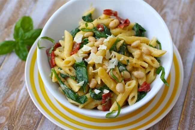 Fresh basil adorns a bowl of Creamy Pasta with White Beans and Spinach