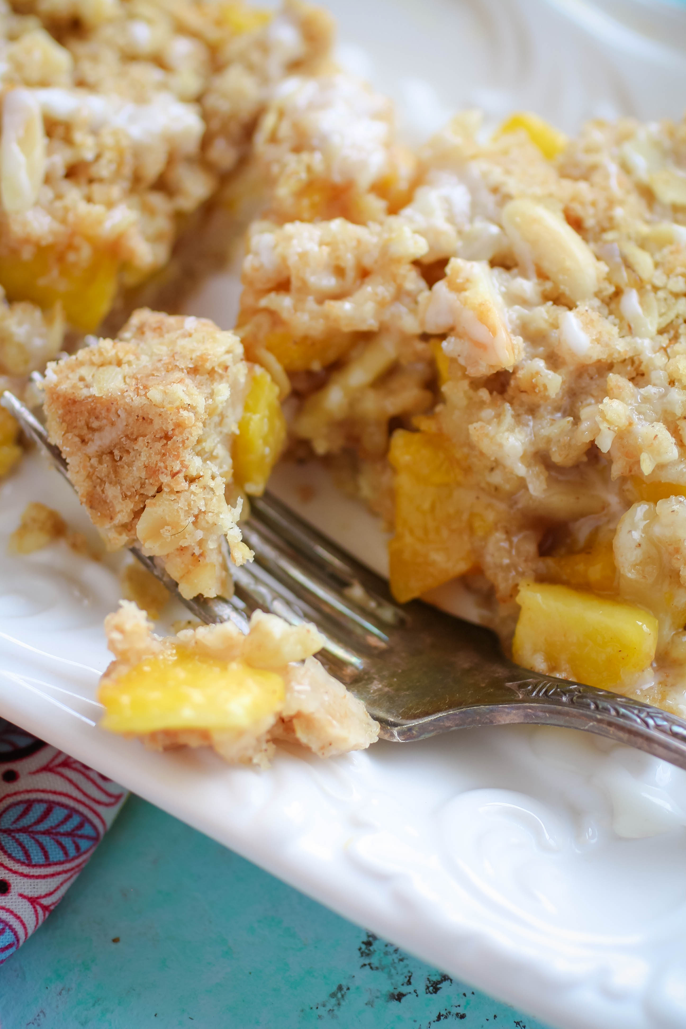 Peach Crumble Squares with Bourbon Glaze are a summertime treat to dig into. Enjoy these Peach Crumble Squares with Bourbon Glaze this summer while peaches are in season.