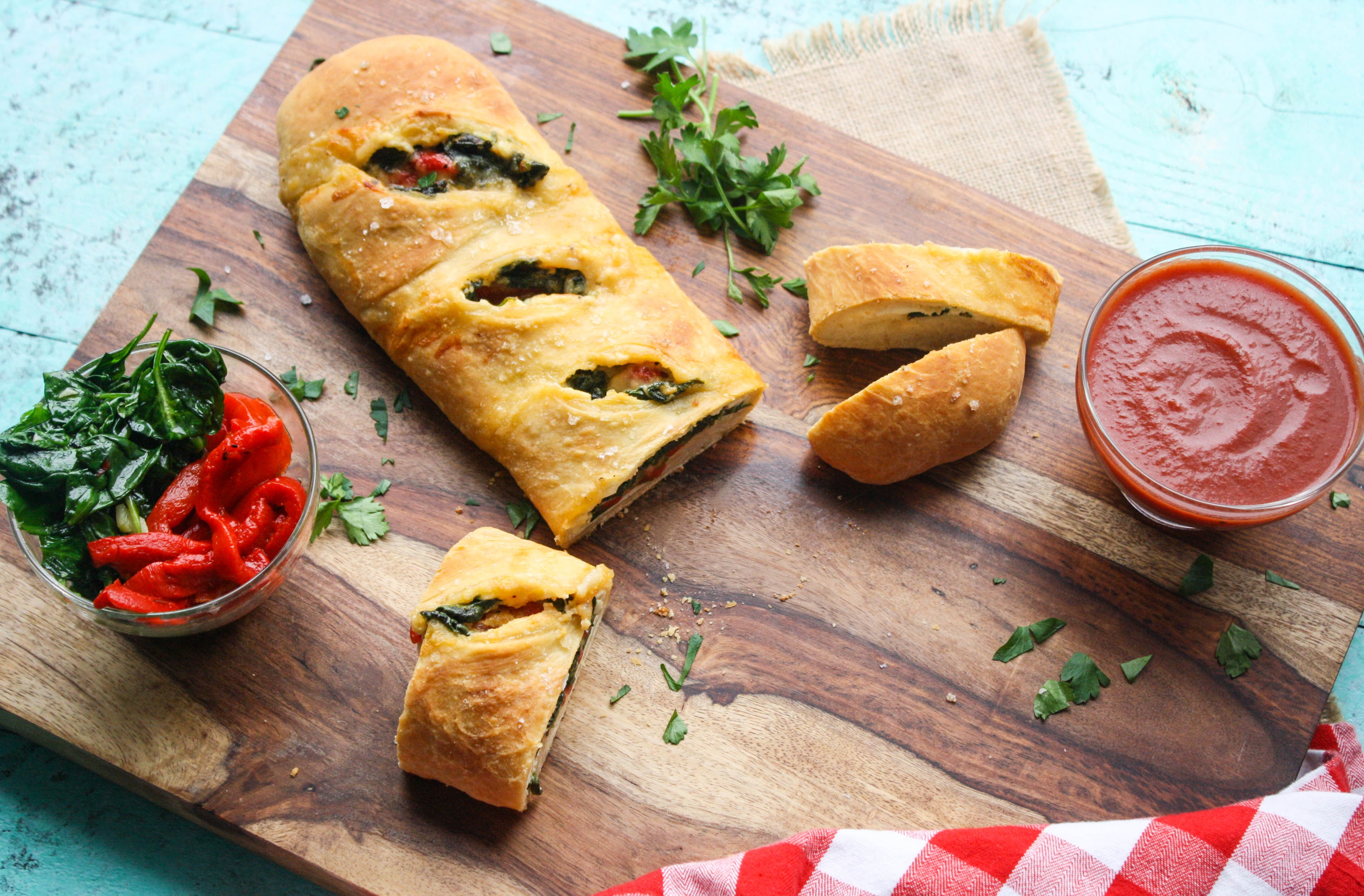 Spinach and Roasted Red Pepper Stromboli is filled with delicious ingredients and it's so fun to serve! You'll love this pizza-like dish.